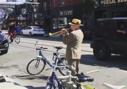 Er steht mit seiner Trompete an der Straße