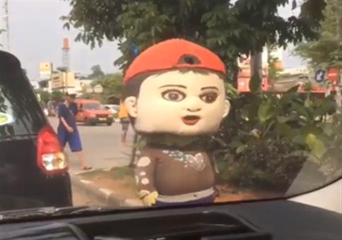 Verstörendes Werbemaskottchen am Autofenster
