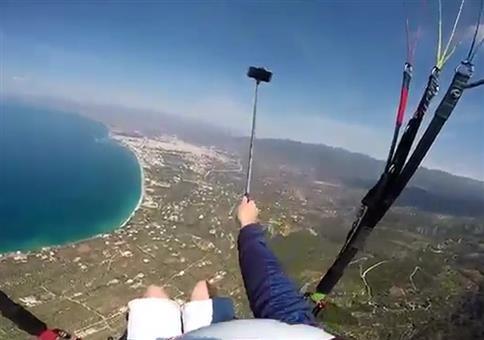 Er hantiert mit dem Selfiestick beim Paragliden