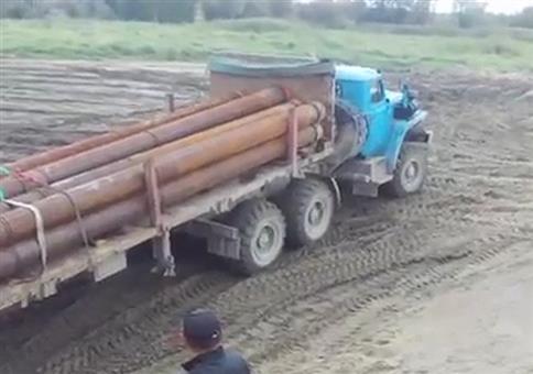 LKW mit langen Rohren fährt auf eine Fähre