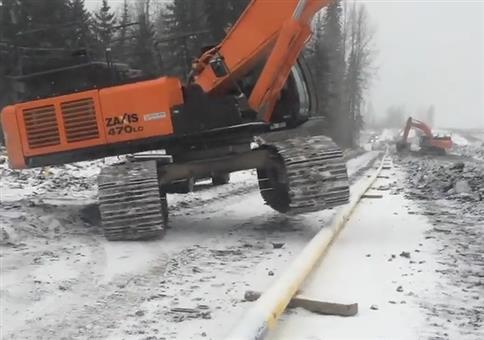 Mit dem Bagger über ein Rohr steigen