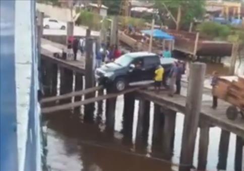 Auto auf losen Planken auf ein Schiff verladen