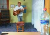 Sprung mit einer Gitarre über einen Stuhl