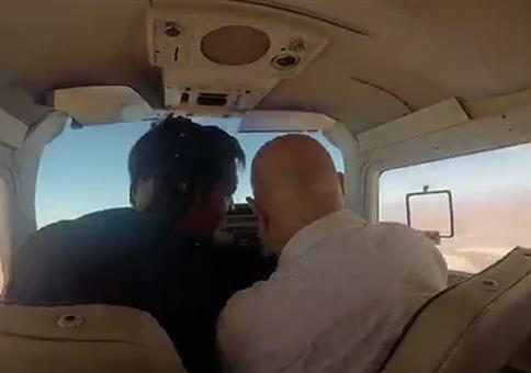 Im Flugzeug das Fenster öffnen um ein Foto zu machen