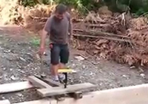 Flasche Bier mit einem Hammer in ein Brett schlagen