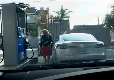 Blondine will an Tankstelle ihren Tesla volltanken