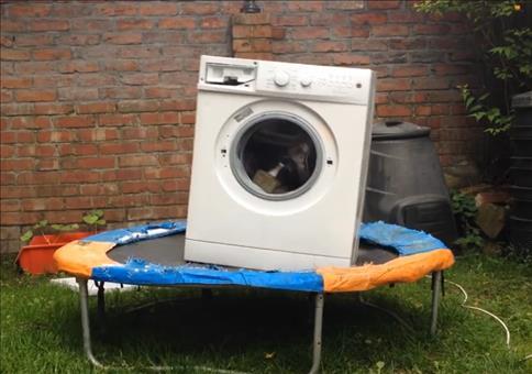 Waschmaschine mit Ziegelsteinen beladen auf einem Trampolin