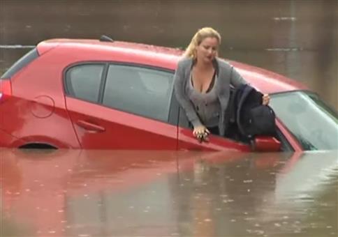 Frau im Auto bei Hochwasser
