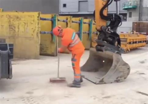 Fleißiger Bauarbeiter fegt den Hof