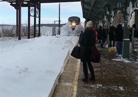 Ein Zug fährt bei viel Schnee in einen Bahnhof ein