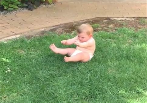 Baby mit einer leichten Phobie vor Gras