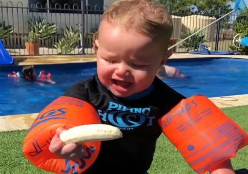 Kind versucht mit Schwimmflügeln eine Banane zu essen