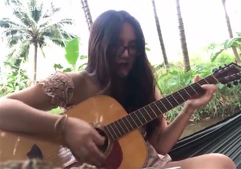 Sie spielt für euch Gitarre am Fluss