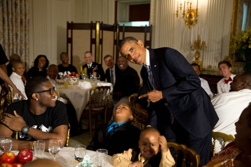 President Barack Obama jokes as a little boy sleeps in his chair during the Father's Day ice cream social in the State Dining Room of the White House, June 14, 2013. Students from the Becoming A Man (BAM) program in Chicago attend. (Official White House Photo by Pete Souza)